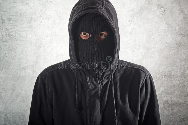 Burglar in black. Burglar concept, thief with balaclava caught in front of the grunge concrete wall stock photos