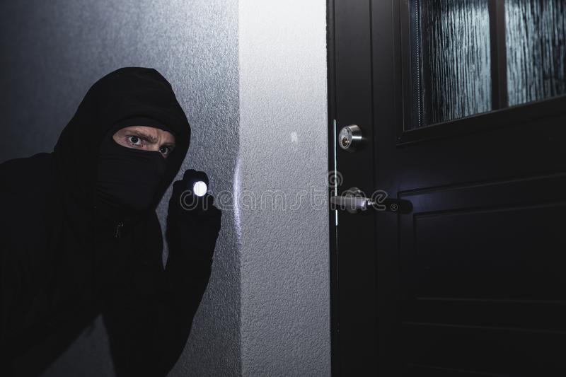 Burglar in mask ready to break in the house at night royalty free stock image