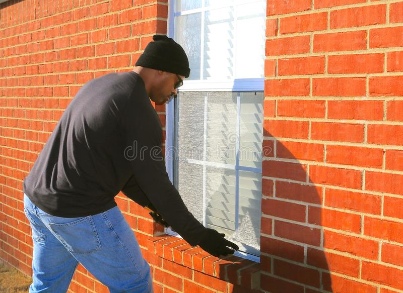 Burglar Breaking in Home Window. African American male in the act of breaking into a home through a window stock image