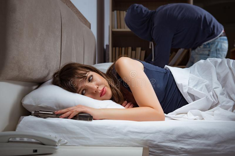 Burglar breaking into house at night to bedroom with sleeping wo. Man stock image