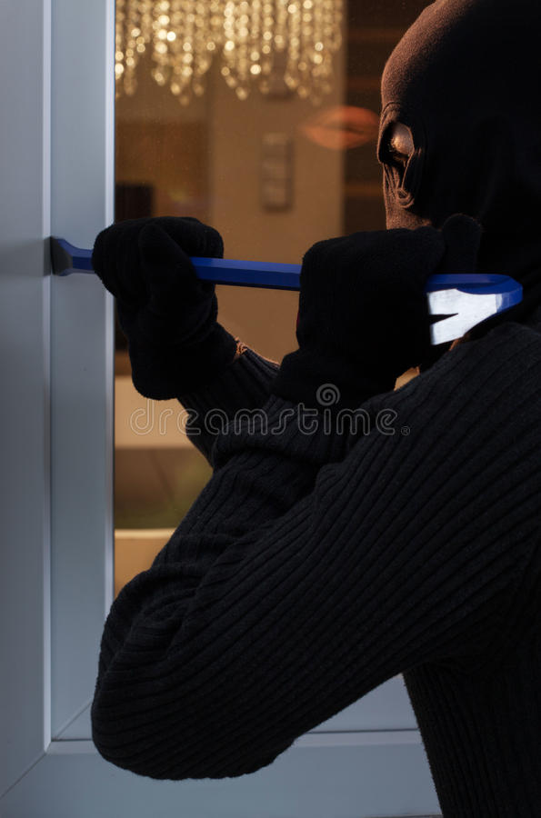 Burglar breaking into the house royalty free stock photography