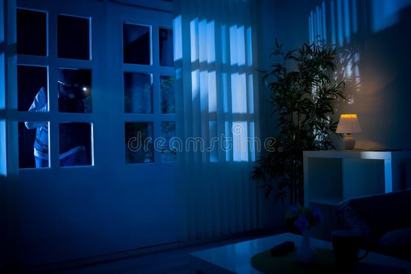 Burglar breaks into house. Through back door stock images