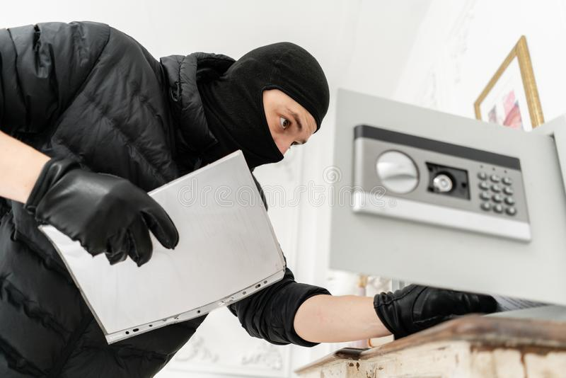 The thief opens the electronic safe. The burglar commits a crime in Luxury apartment with stucco. Thief with black. The burglar commits a crime in Luxury royalty free stock image