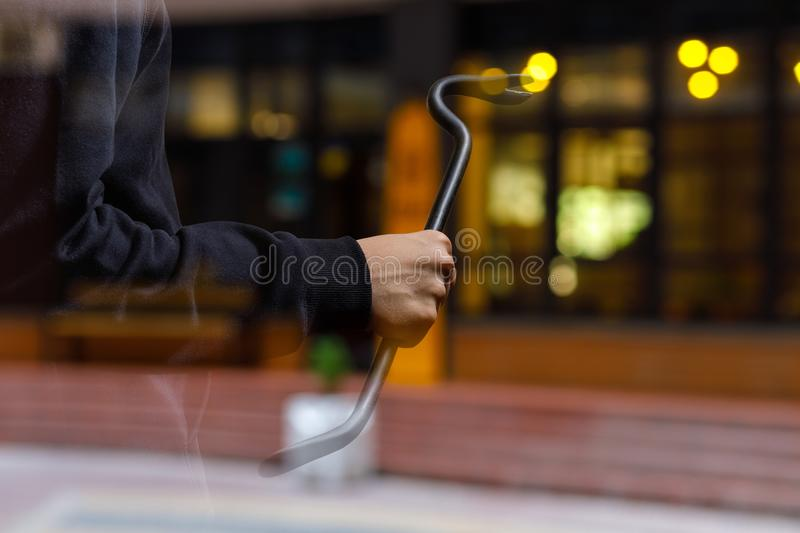Burglar with a crowbar on the background of the shop. Burglar with a crowbar on the background of the shop window stock photos