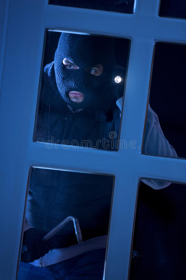 Burglar with crowbar breaking into a house. Through glass door royalty free stock images