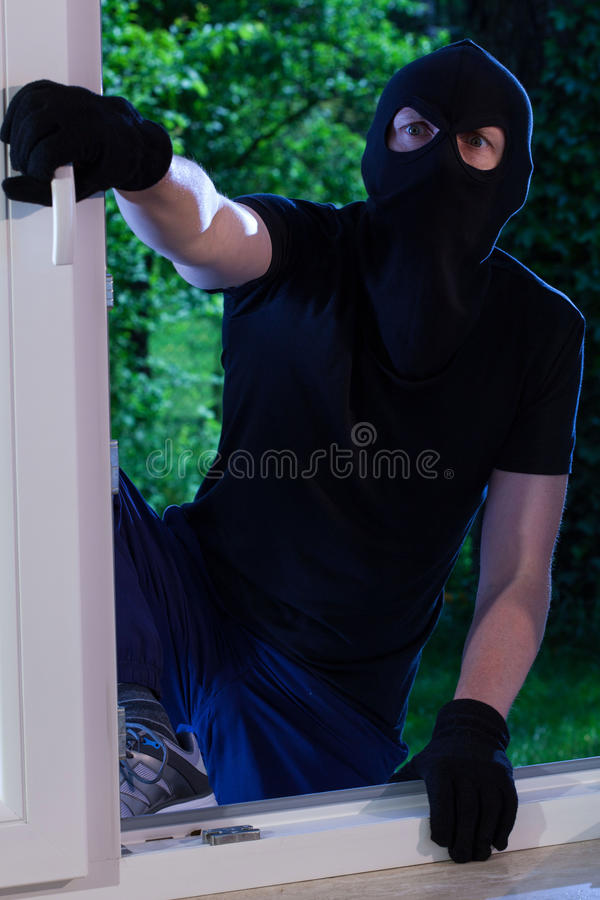 A burglar enters the house. Through the window royalty free stock images