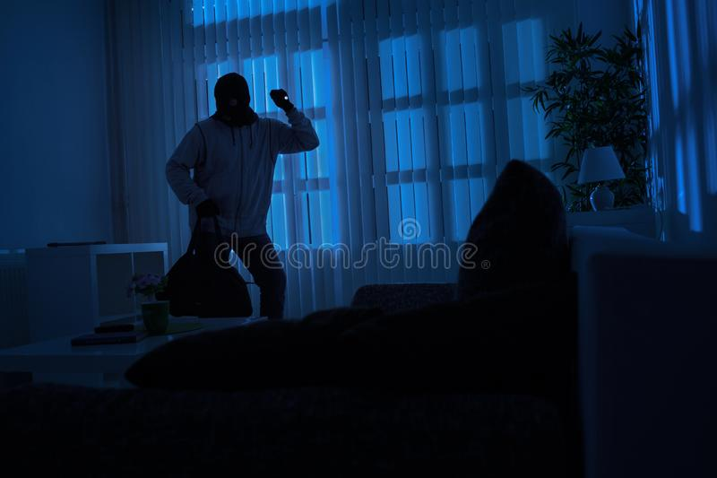Burglar with flashlight and crow bar royalty free stock photo