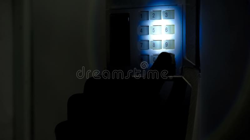 Burglar with flashlight trying to disarm security alarm system, housebreaking royalty free stock images