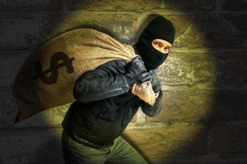 Burglar with full bag of money is catched with flash light at night royalty free stock images
