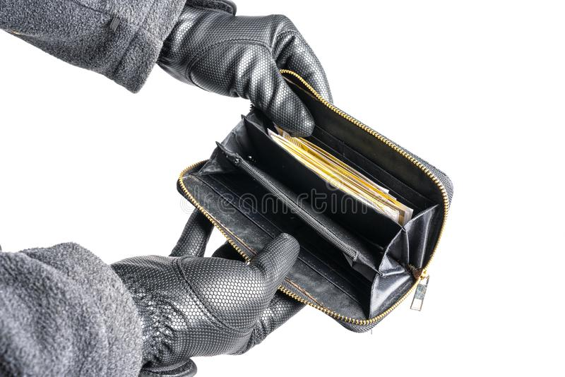 Burglar with gloves tries to steal money from a purse stock photography