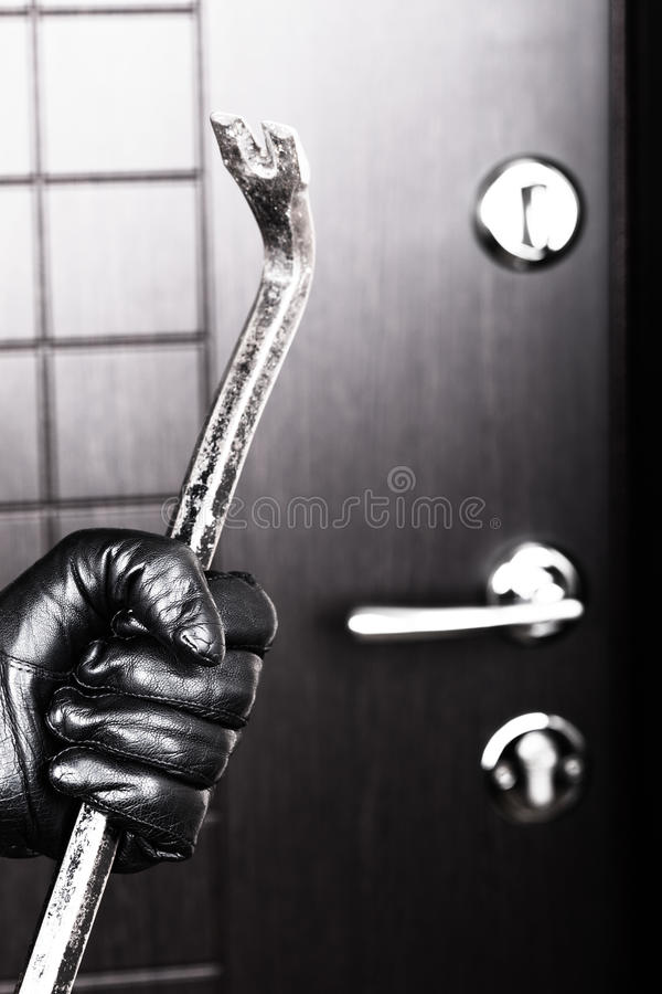 Burglar hand holding crowbar break opening door stock image