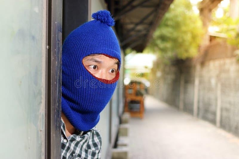 Burglar hiding behind entrance before burglary. Criminal concept royalty free stock image