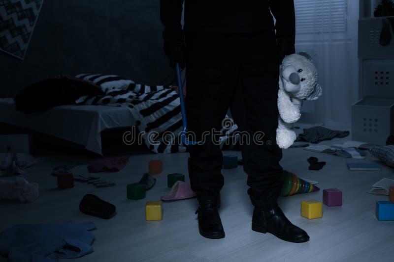 Burglar holding a teddy bear royalty free stock photography