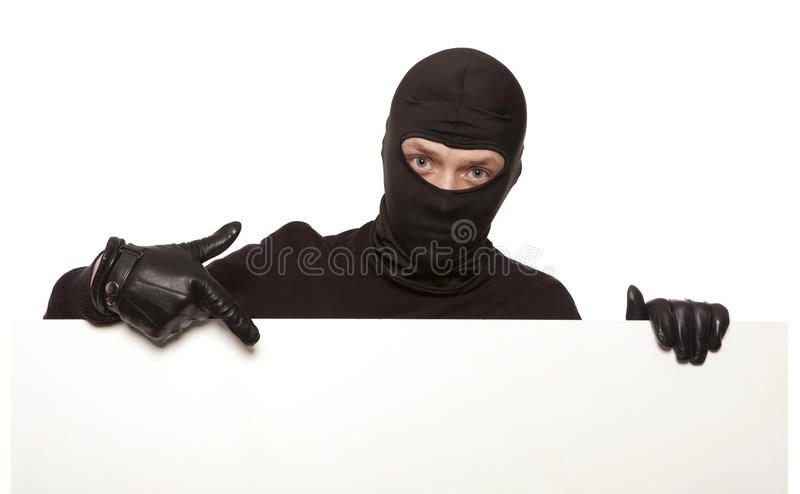 Burglar, ninja isolated. Ninja. Robber hiding behind a empty white sign with space for text. Isolated on white background stock images