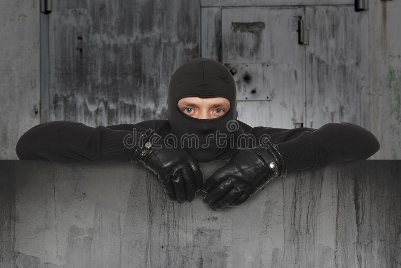Burglar, Ninja, Robber. Ninja. Robber hiding behind a empty sign with space for text stock photography