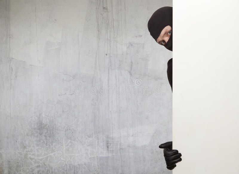 Burglar, Ninja. Ninja. Robber hiding behind a empty white sign with space for text stock image