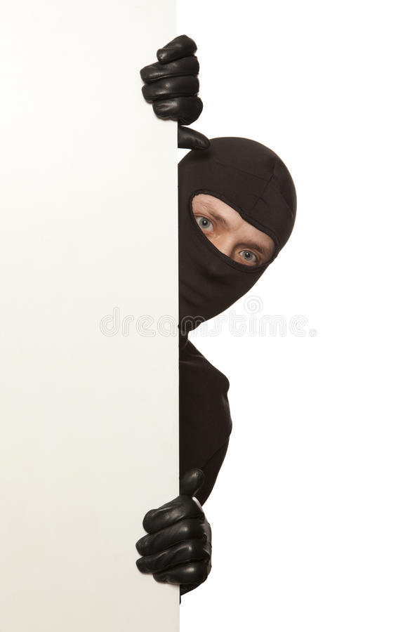 Burglar. Ninja. Robber hiding behind a empty white sign with space for text. Isolated on white background stock images