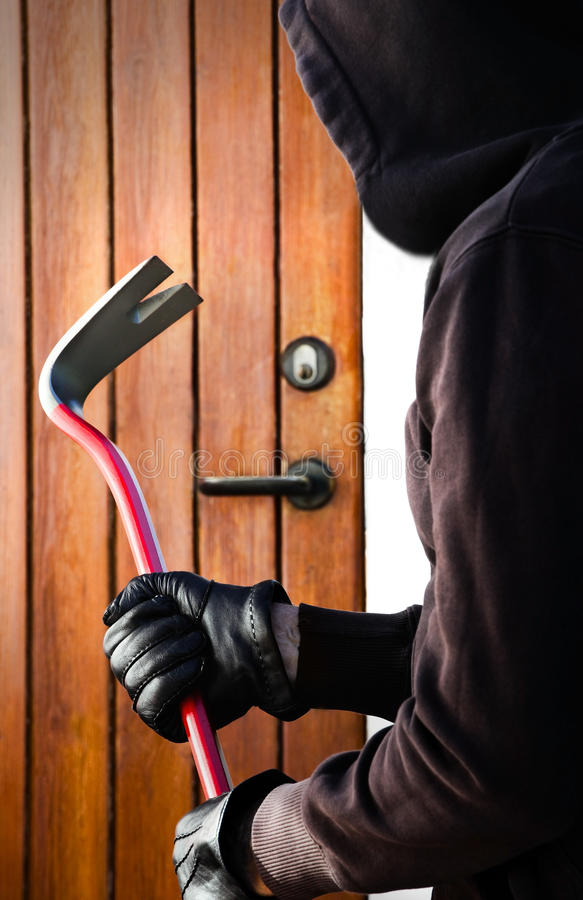 The Burglar. Photo of a Burglar hand holding crowbar royalty free stock images