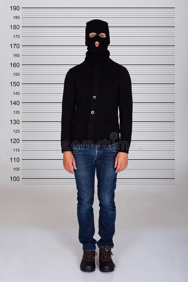 Burglar Standing Against Police Lineup stock photography