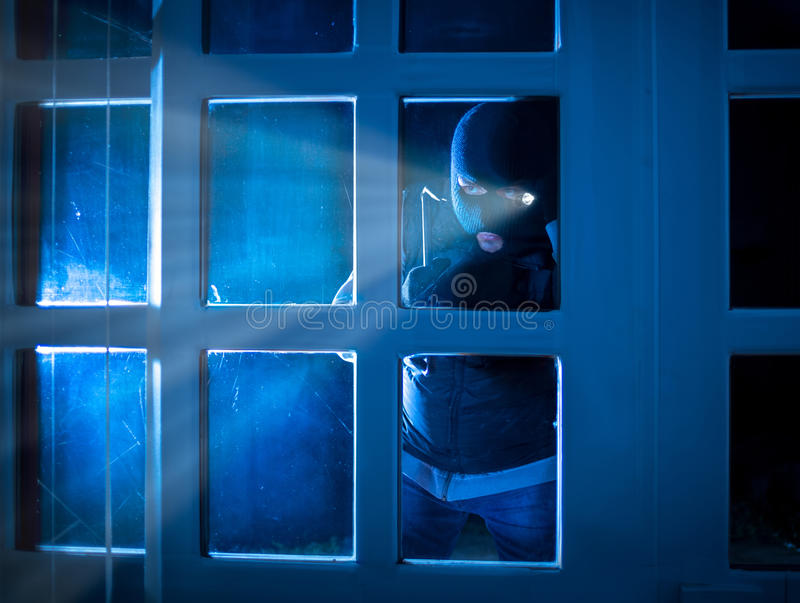 Burglar standing in the dark outside and peering inside. Through glass door royalty free stock images