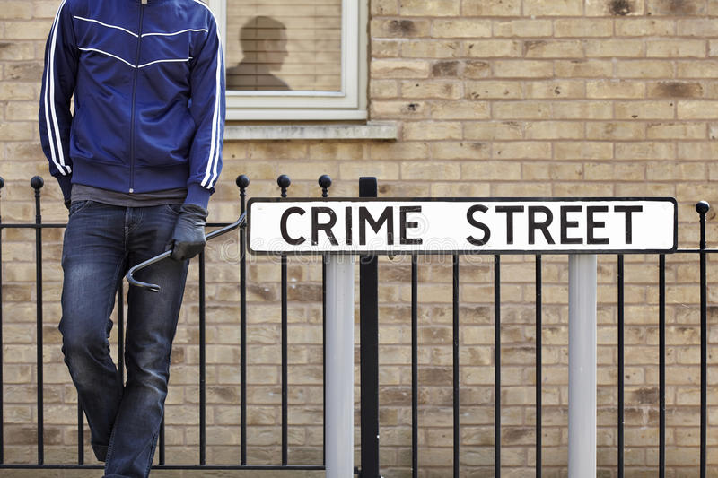 Burglar standing on street with crowbar stock images