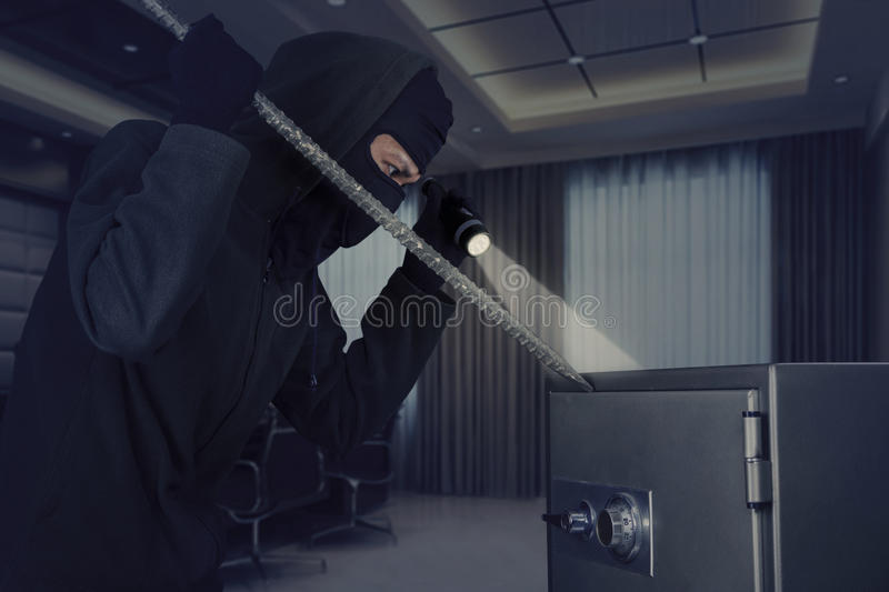 Burglar stealing a safe deposit box stock photography