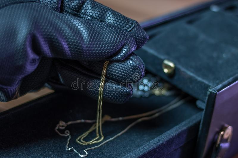 A burglar steals jewelry from a casket. With gloves stock photos