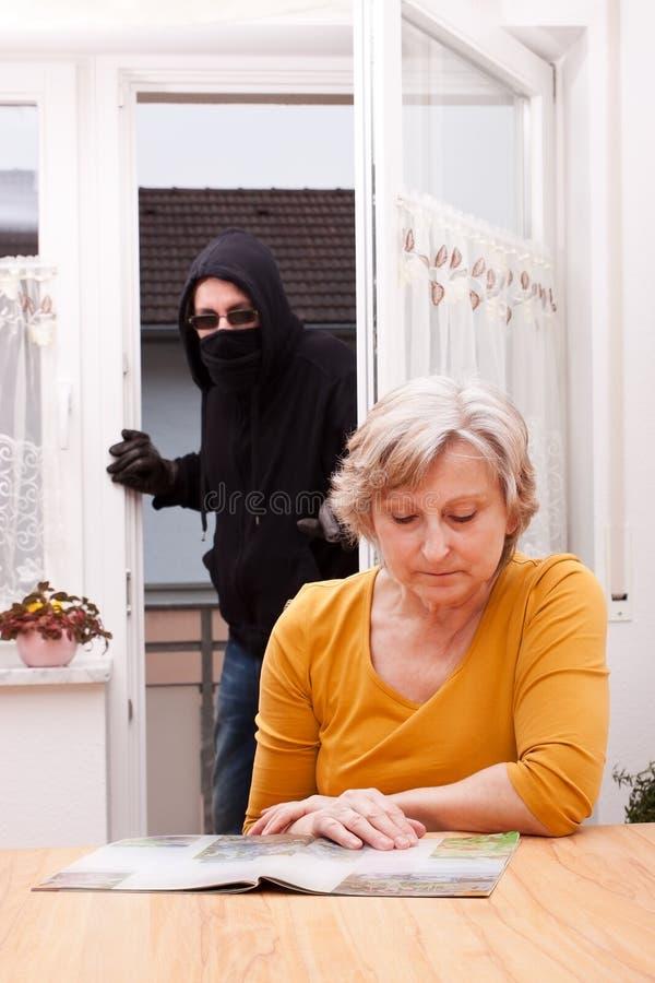Burglar surprise unwary senior royalty free stock photo
