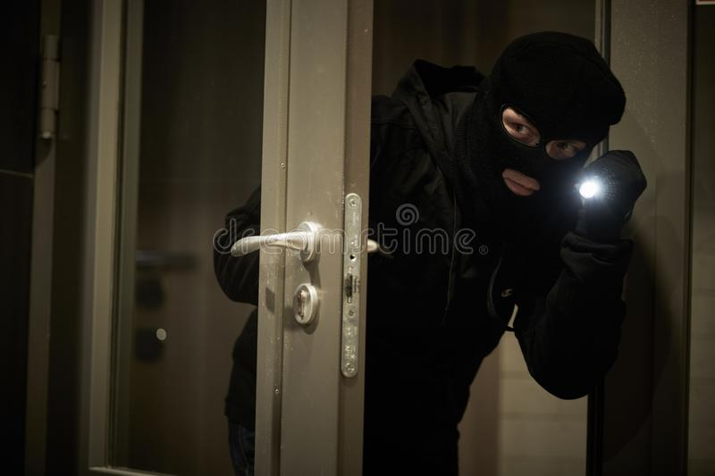 Burglar thief in mask. break-in of an apartment. stock image
