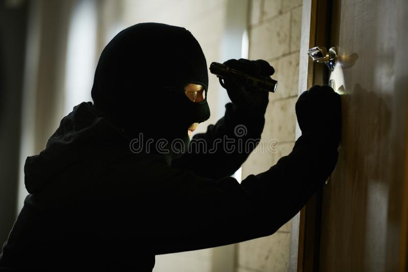 Burglar thief in mask. break-in of an apartment. royalty free stock image