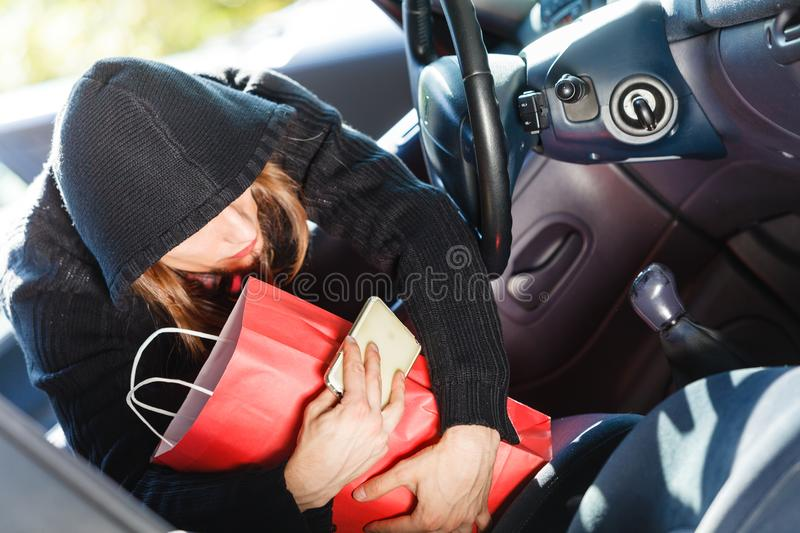 Burglar thief stealing smartphone and bag from car. Anti theft system problem concept. Burglar thief man wearing black clothes breaking into car, stealing stock images
