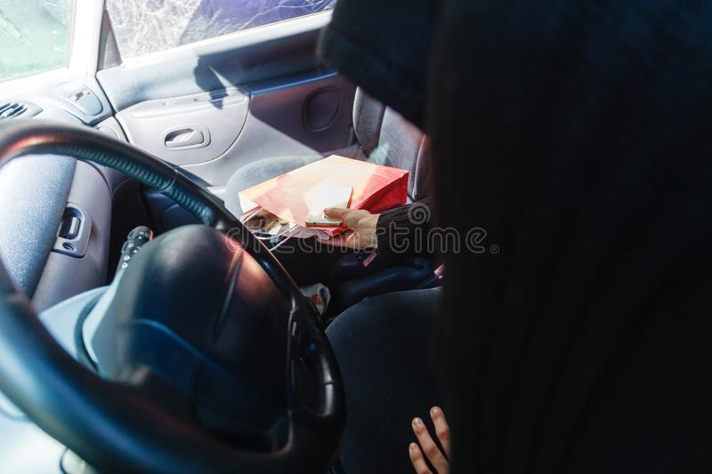 Burglar thief stealing smartphone and bag from car. Anti theft system problem concept. Burglar thief man wearing black clothes breaking into car, stealing royalty free stock image