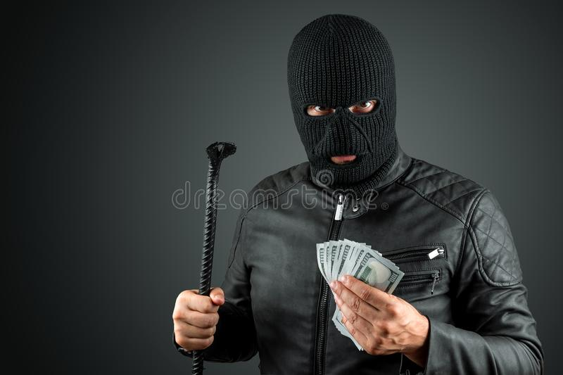 Burglar, a thug in a balaclava holds dollars in his hands on a dark background. Robbery, hacker, crime, theft. Copy space stock images