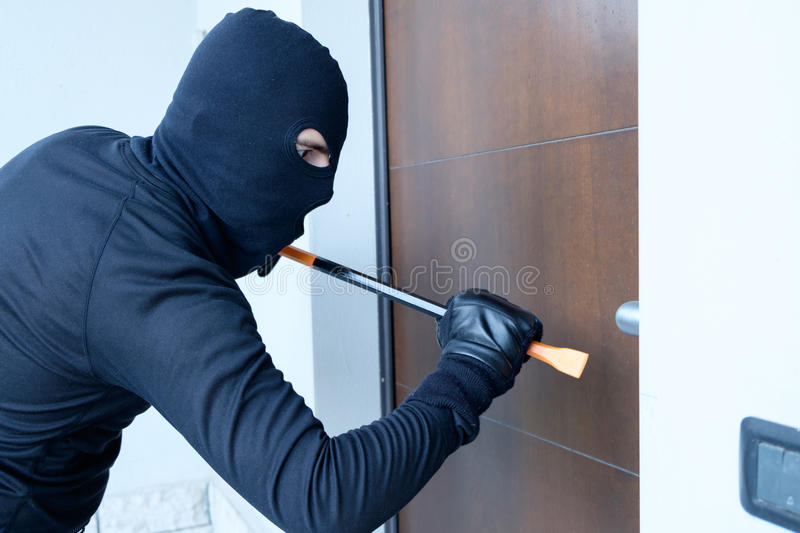 Burglar trying to force a door lock royalty free stock images