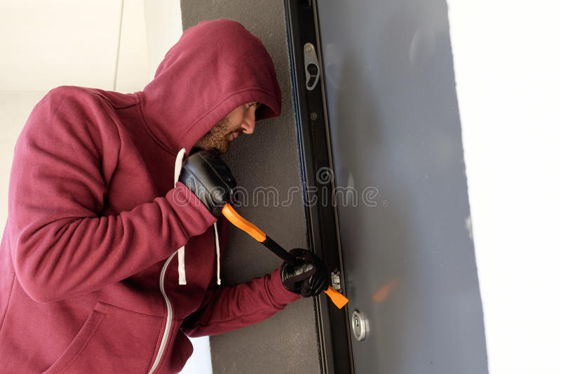 Burglar trying to force a door lock. Using a crowbar stock photo
