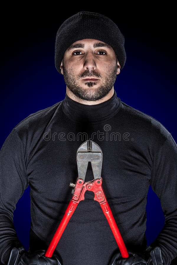 Burglar. A burglar wearing black clothes holding huge wire cutters over black background stock photo