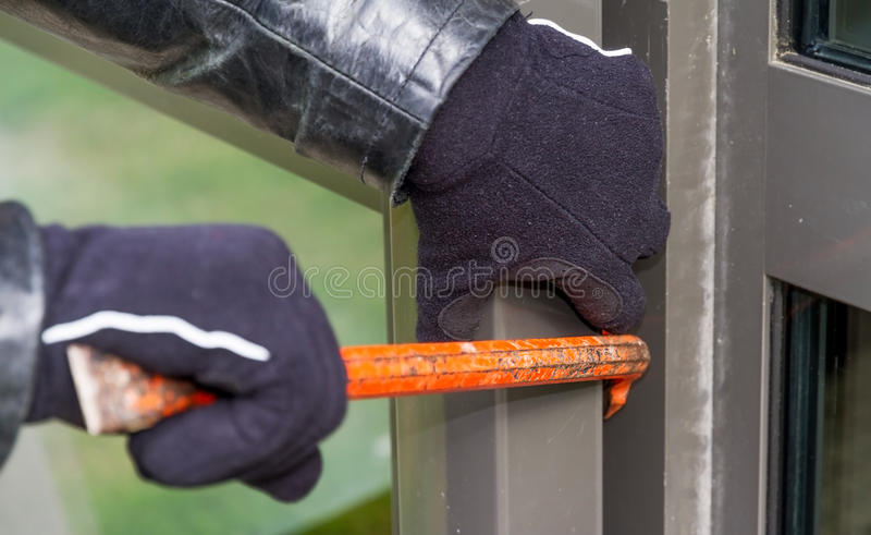Burglar wearing leather coat breaking in a house vector illustration