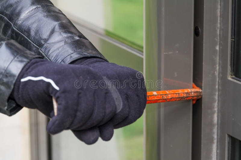 Burglar wearing leather coat breaking in a house stock photo