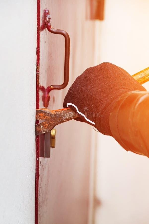 Burglar wearing leather coat breaking in a house stock illustration