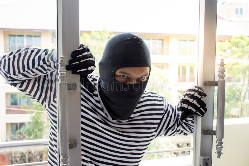 Burglarize try to break into the room to steal stock photography