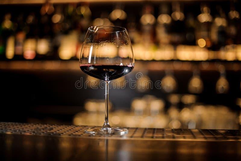Burgonya szkło wypełniający czerwone wino na prętowym kontuarze przeciw złotemu zdjęcie royalty free