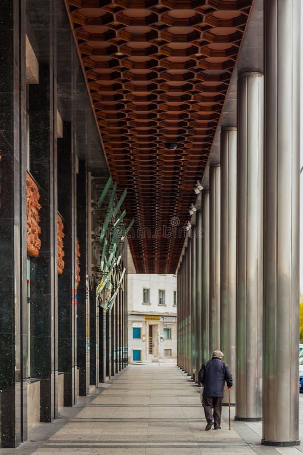 """BURGOS CASTILLA LEÃ """"N/SPANIEN - DECEMBER 7 2019: Ensam gamal man med rottingen som går i staden med kolonner royaltyfri fotografi"""