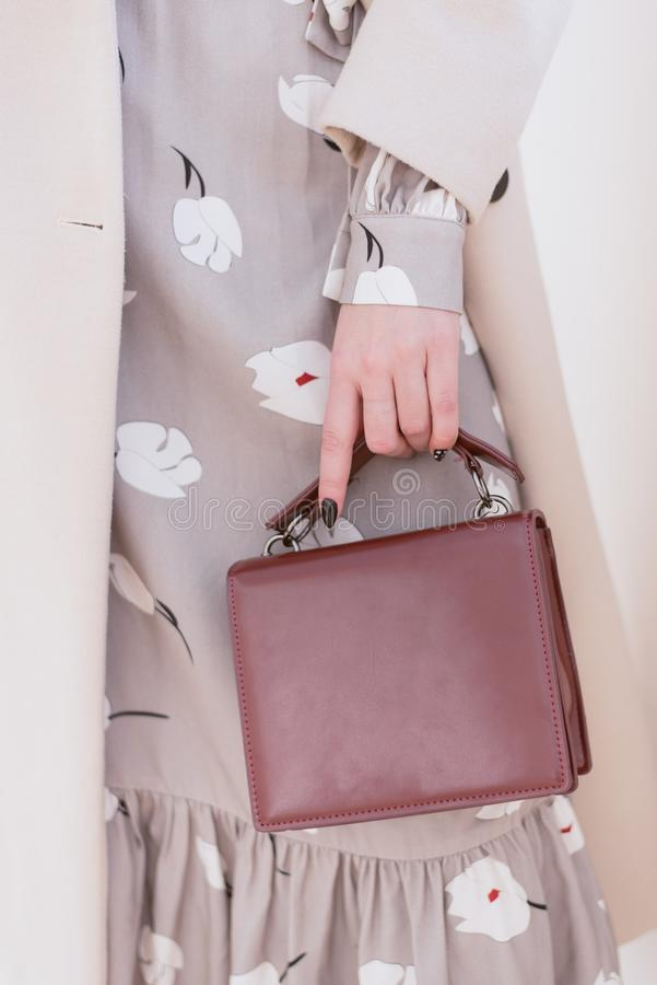 Burgundy bag in hand. stock photography