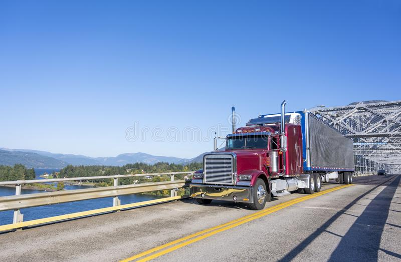 Burgundy big rig classic semi truck with refrigerated shiny semi. Classic American big rig burgundy semi truck with refrigerated semi trailer with reefer unit on royalty free stock photography