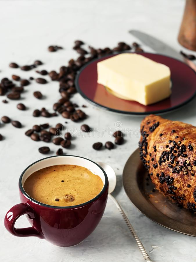 Burgundy color coffee cup with espresso and croissant. In the background are fresh coffee beans, butter and cezve. Located on a. Gray background. Close-up stock photography