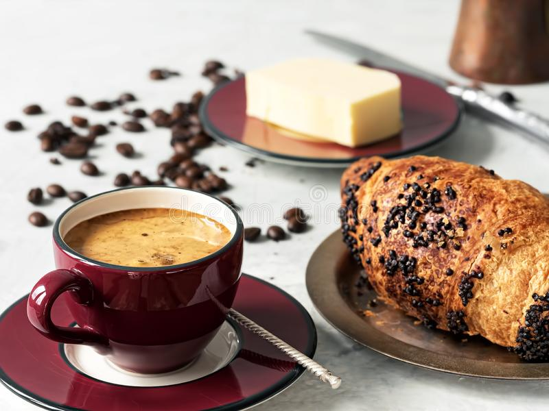 Burgundy color coffee cup with espresso with croissant. In the background are fresh coffee beans, butter and cezve. Located on a. Gray background. Close-up stock photos
