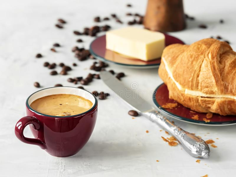 Burgundy color coffee cup with espresso with croissant. In the background are fresh coffee beans, butter and cezve. Located on a. Gray background. Close-up stock photography