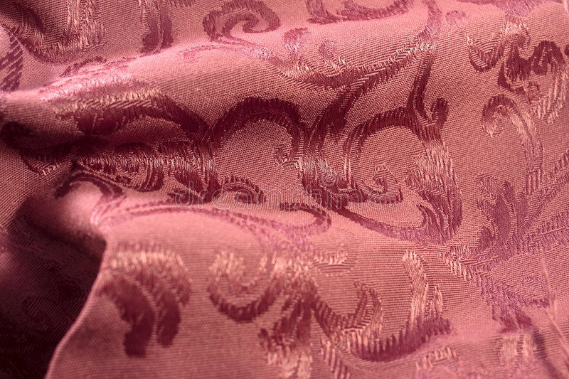 Burgundy Damask Fabric. Deep burgundy colored damask fabric shows the stitches of the satin leaf tone on tone pattern. There are some soft folds in the fabric royalty free stock images