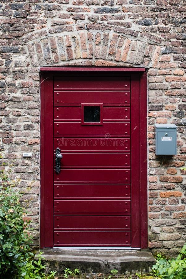 A burgundy door on a brick building in a German village stock photos