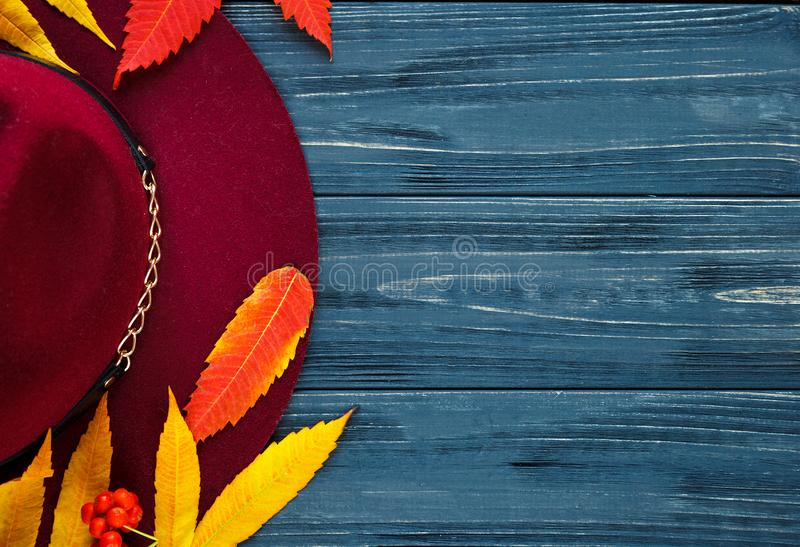 Burgundy  or marsala color hat on a gray wooden background with autumn yellow, red leaves and berries. Flat lay, copyspace royalty free stock photography